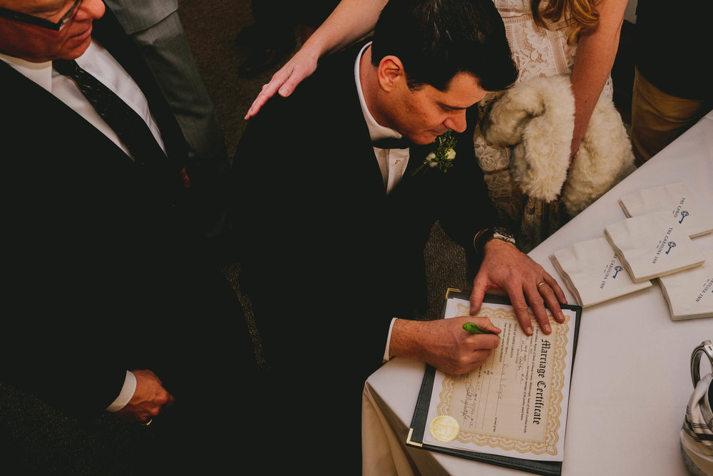 the bride and groom signing their marriage license