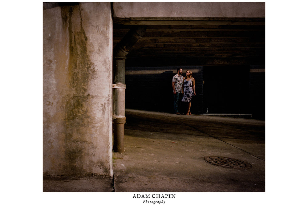 Couple talking under a bridge in some beautiful sunlight during their engagement photos in downtown Wilmington, North Carolina