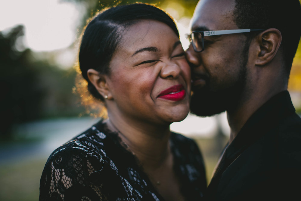 Couple laughing during engagement photos at North Carolina Museum of Art