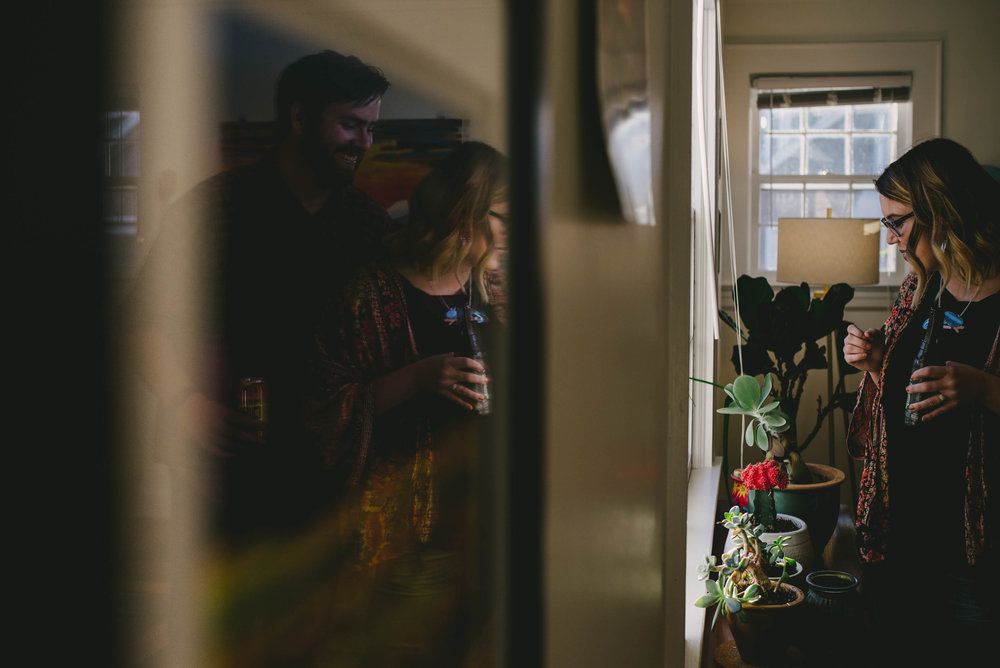 Couple drinking beers and admiring their plants at home during their engagement photos in Greensboro, North Carolina