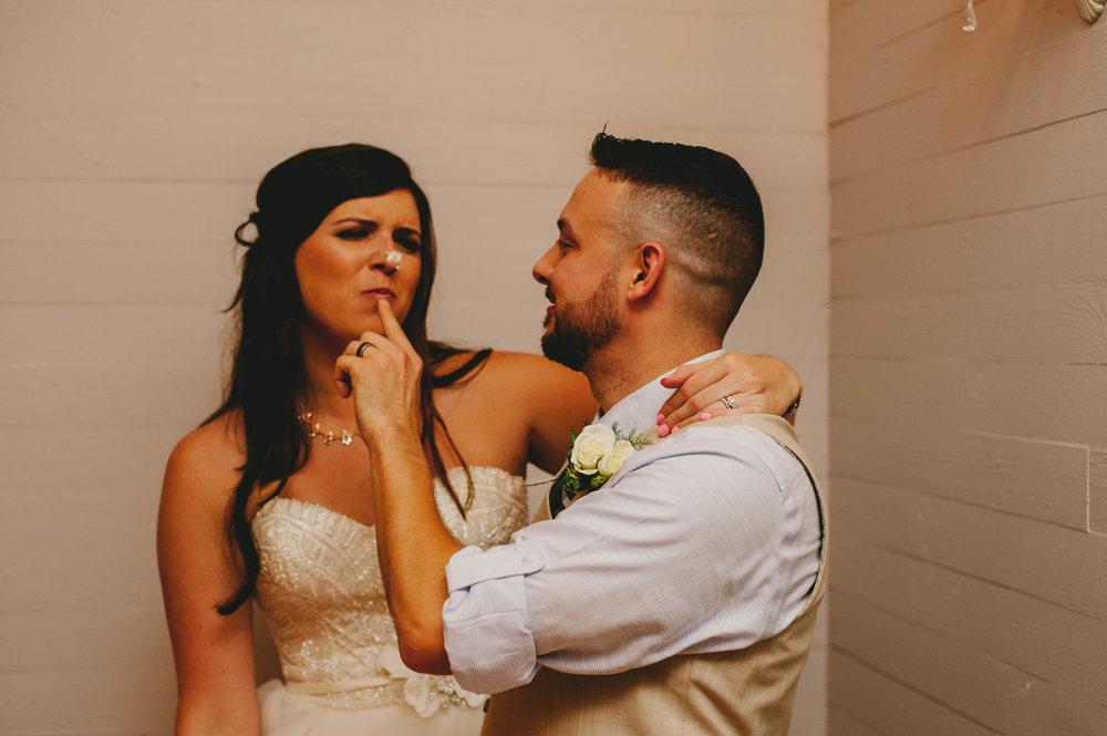 groom wipes cake frosting on brides nose