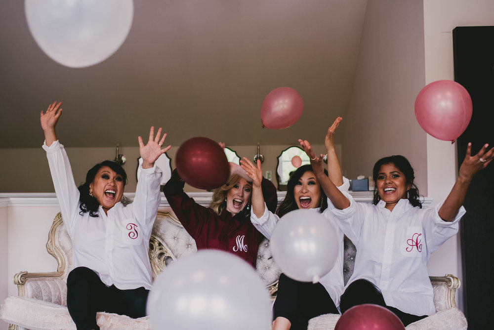 bride and bridesmaids celebrating with a balloon toss
