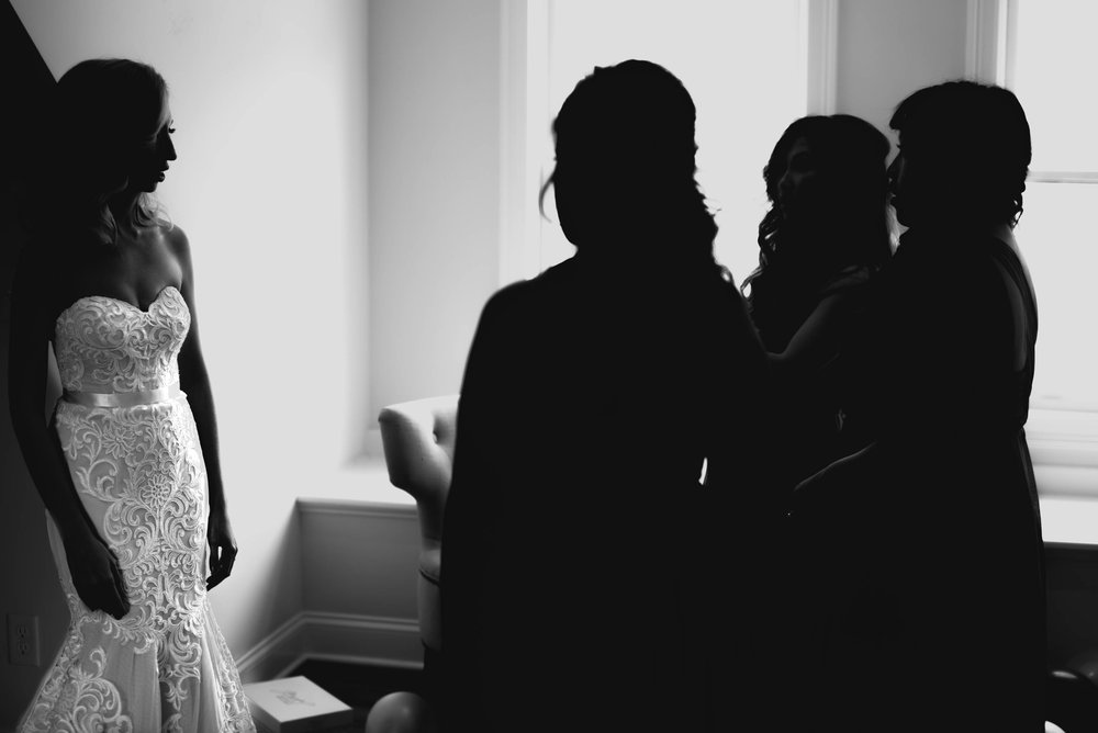 black and white wedding photo of bride as her bridesmaids are loving on her dress