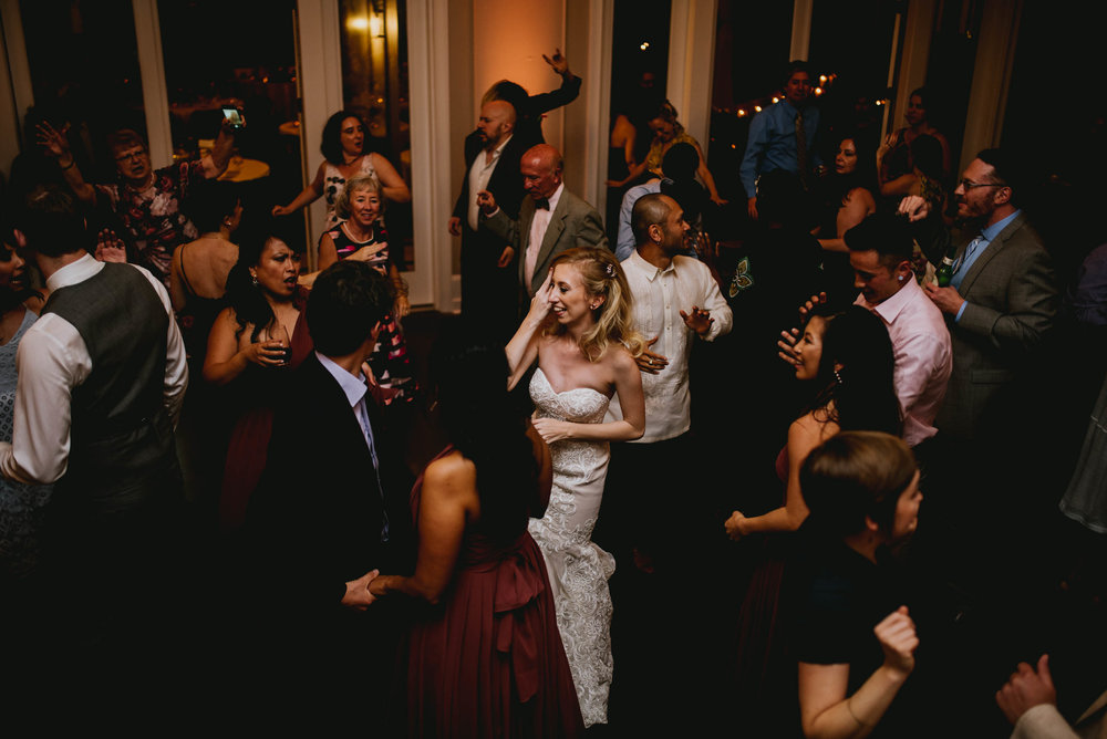 bride and groom surrounded by friends dancing during reception