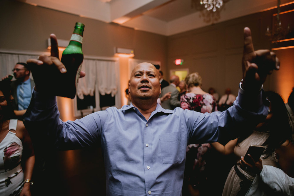 wedding guest dancing with beers in hand