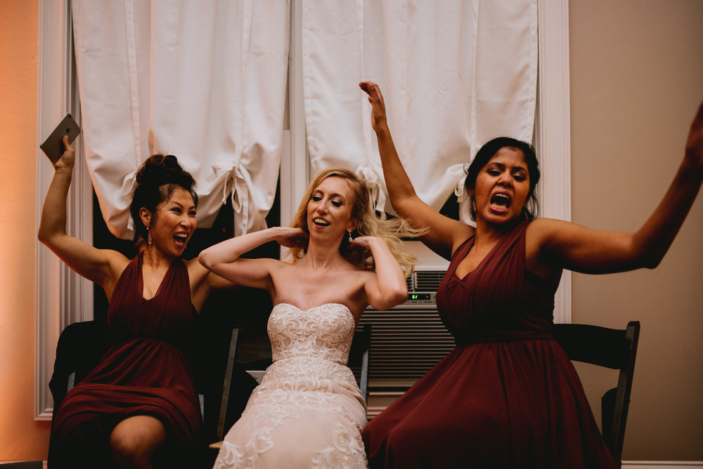 bride and bridesmaids trying to cool off after dancing