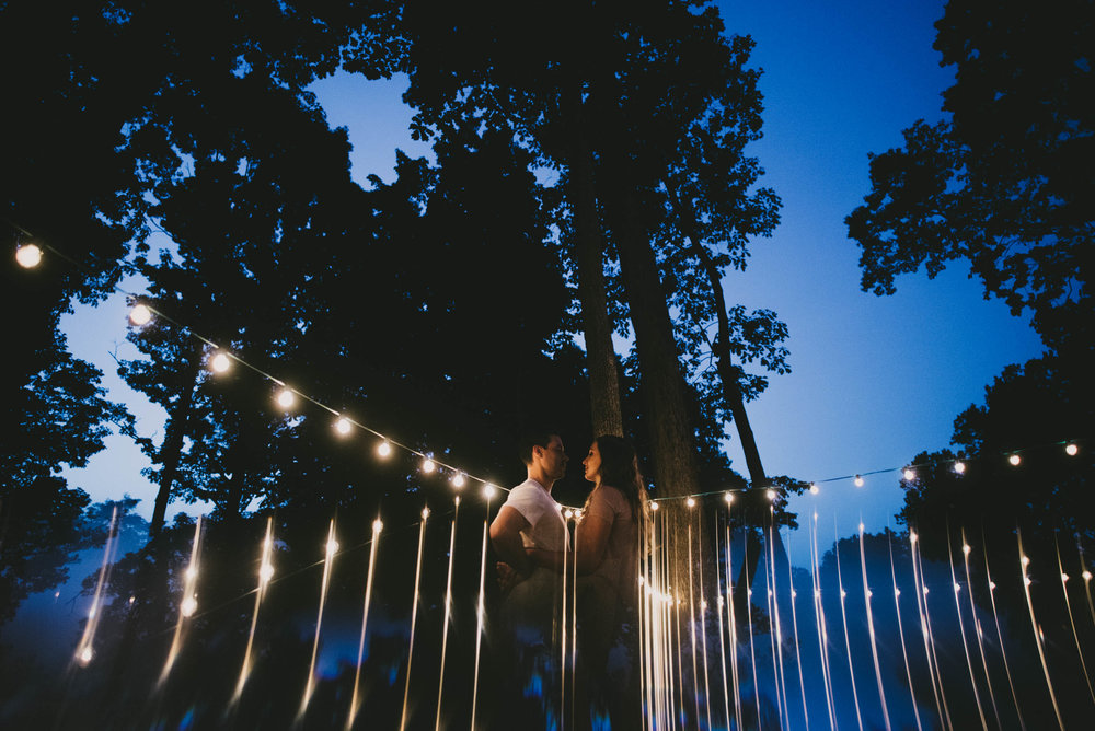 couple surrounded by reflection of market lights, sky and trees during their engagement session in Durham, North Carolina
