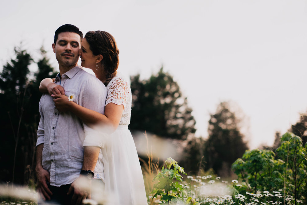 couple embracing in a field of wildflowers during their Eno River Park engagement