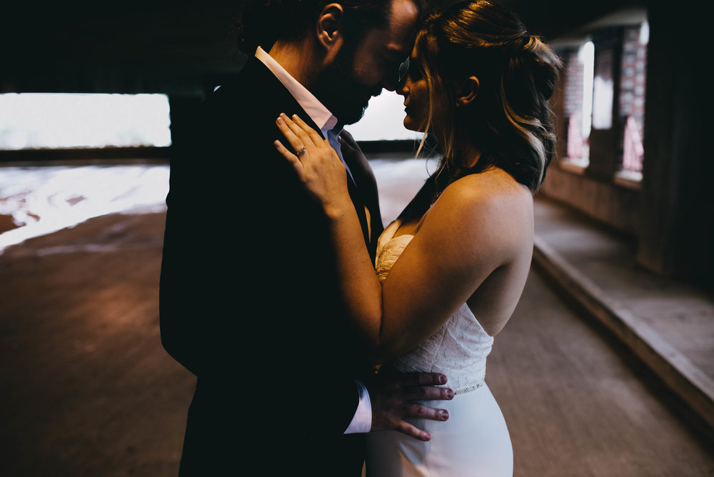 bride and groom embracing during portraits in downtown Raleigh parking garage