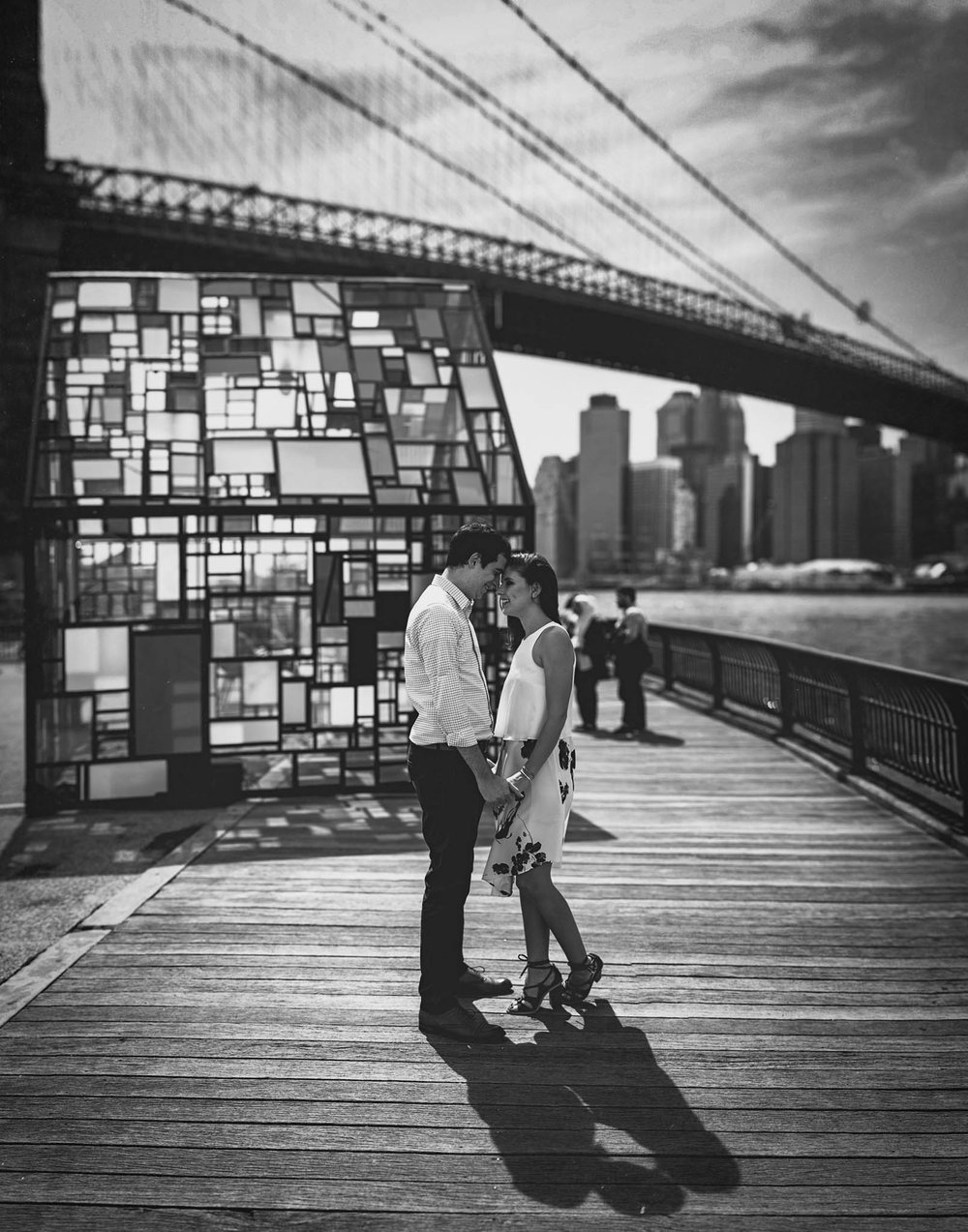 couple together under the brooklyn bridge during engagement photos