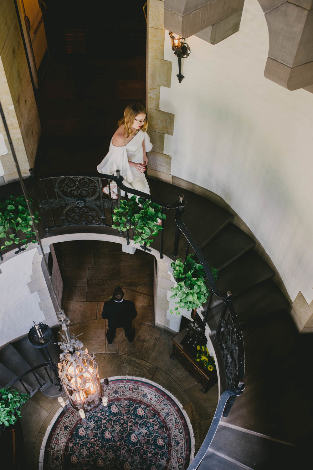 bride walking down spiral staircase at graylyn mansion to meet her husband