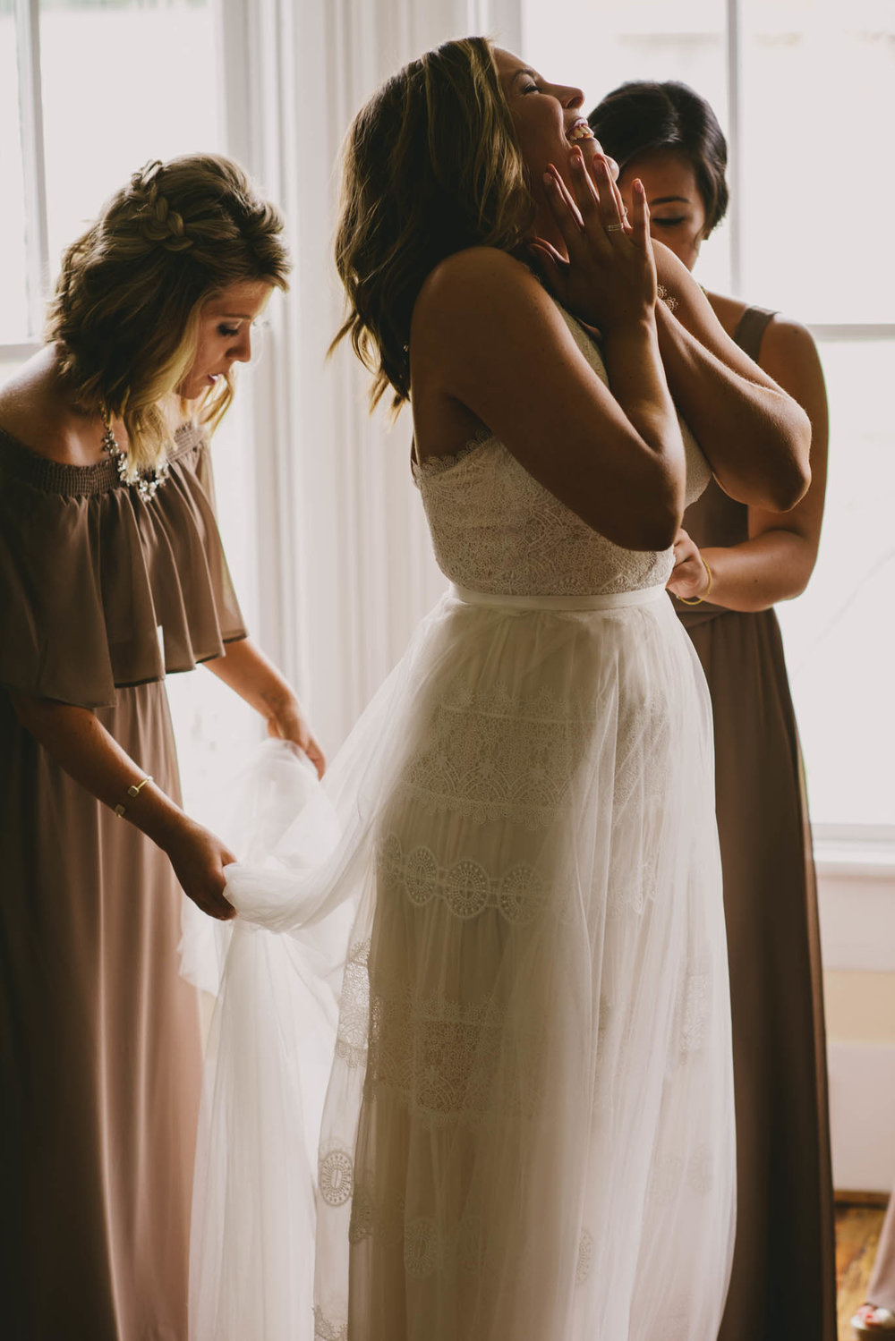 bride and her bridesmaids putting on the final touches of the dress before the wedding