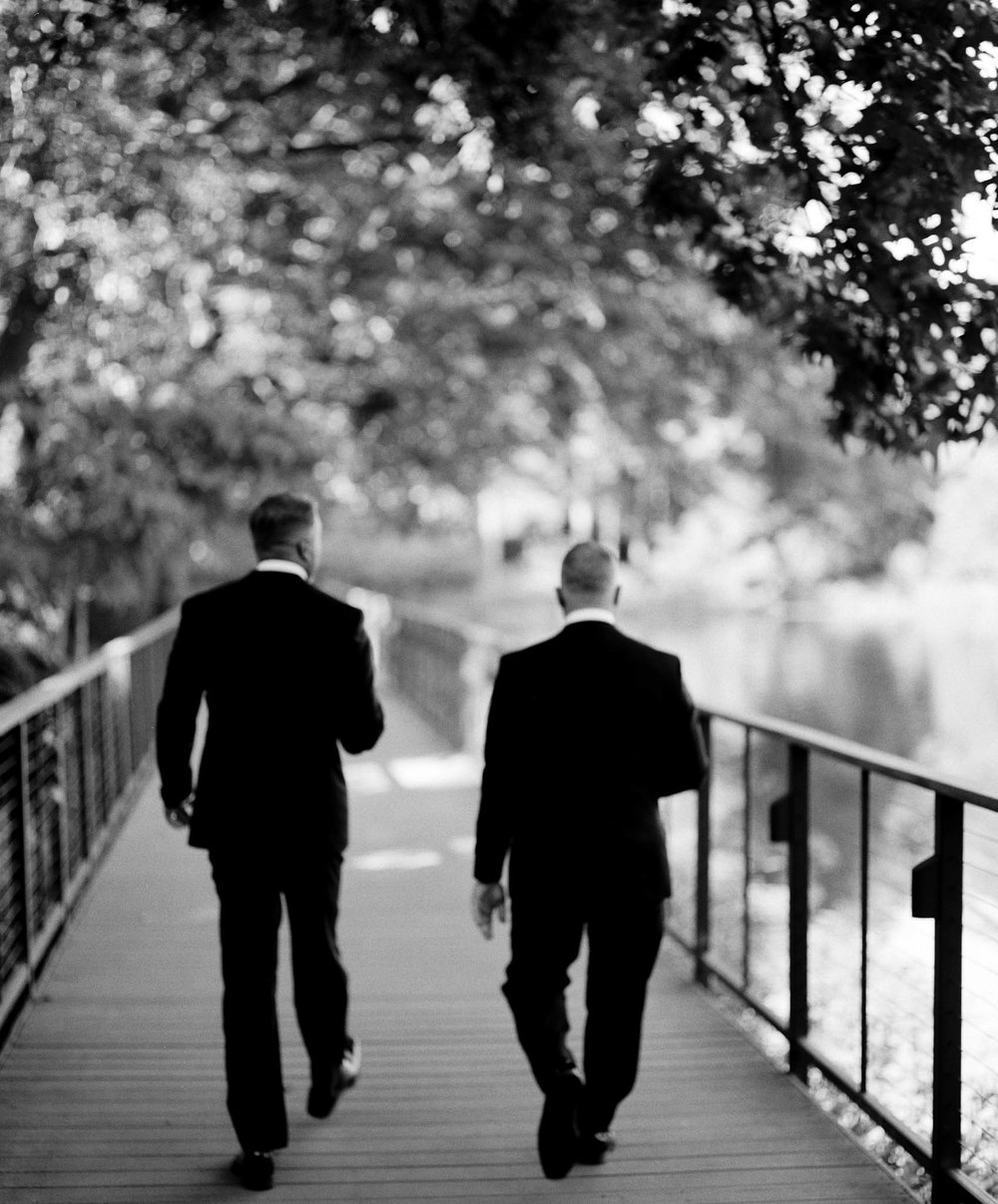 two grooms taking a walk by a pond after their Umstead Hotel wedding ceremony