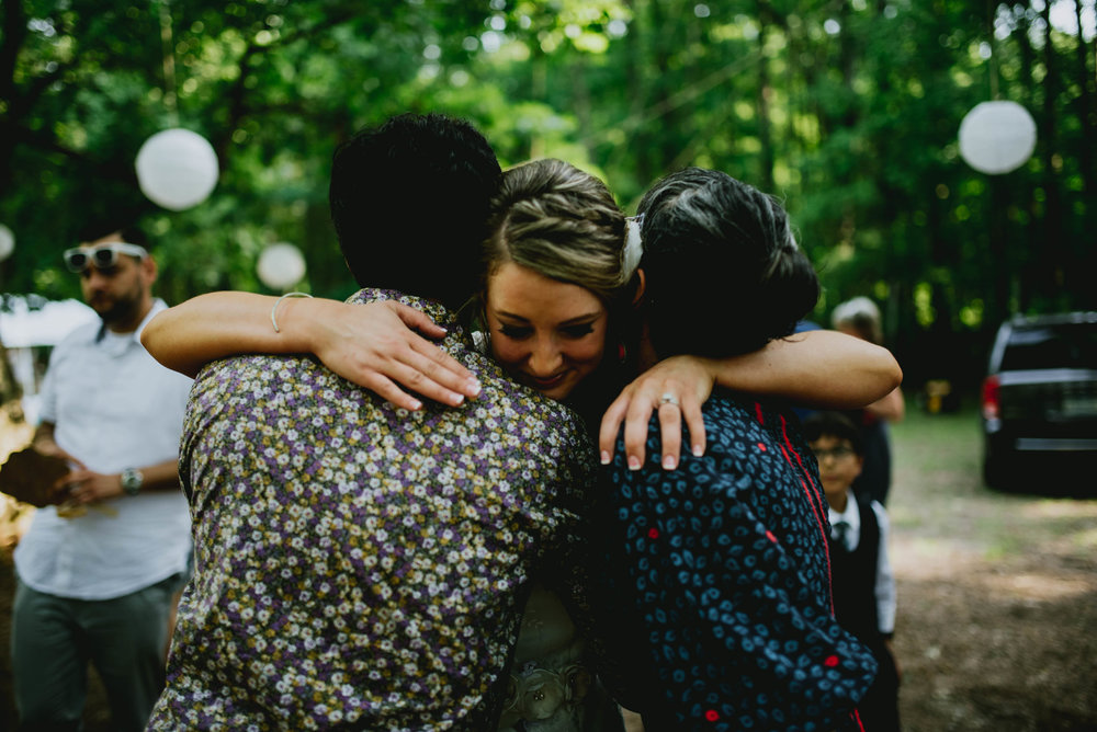 bride sharing a big hug with two wedding guests