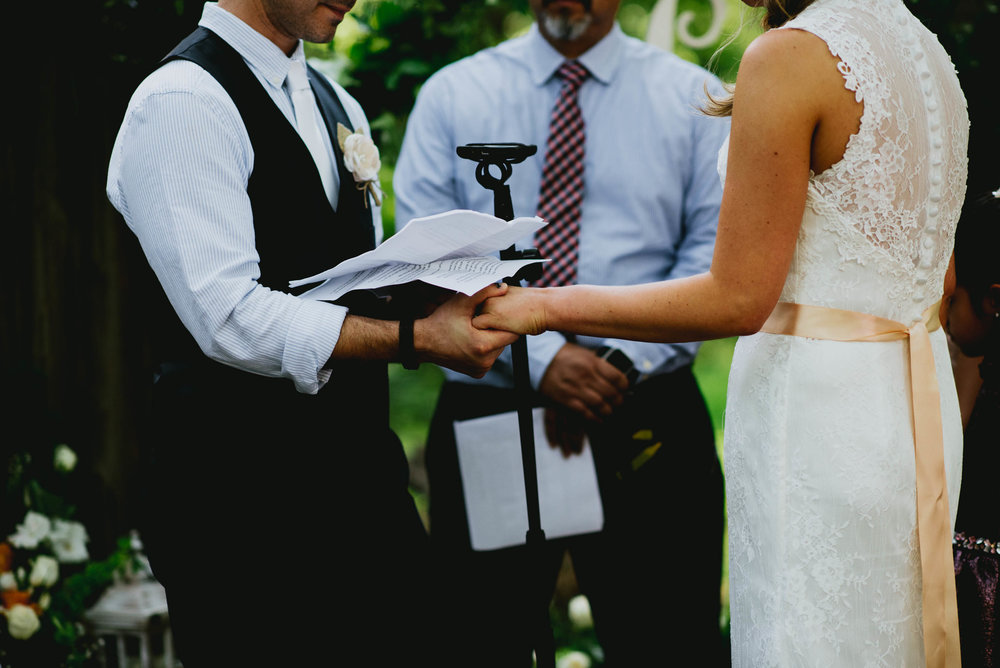 bride and groom holding hands during vow reading
