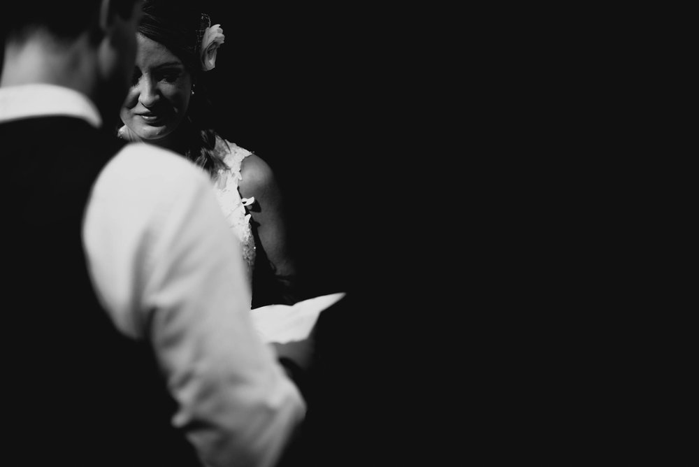 bride listening intently and smiling during grooms vow reading