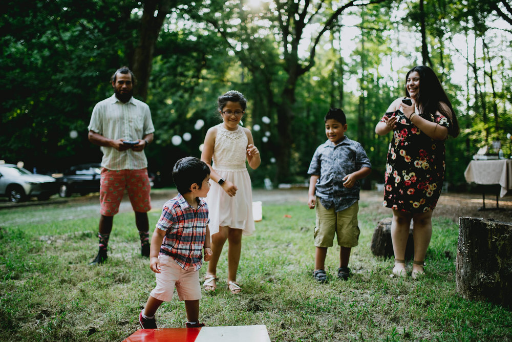 families playing cornhole during duke forest wedding reception