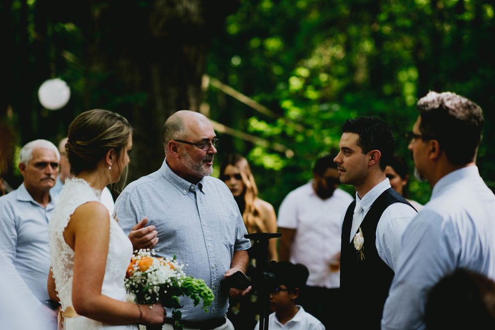 father of the bride sharing some words with guests and groom before the wedding ceremony