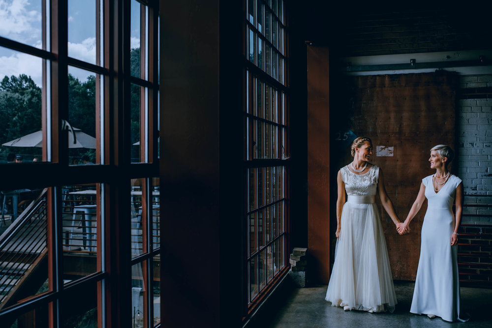 brides standing in the window light of the haw river ballroom