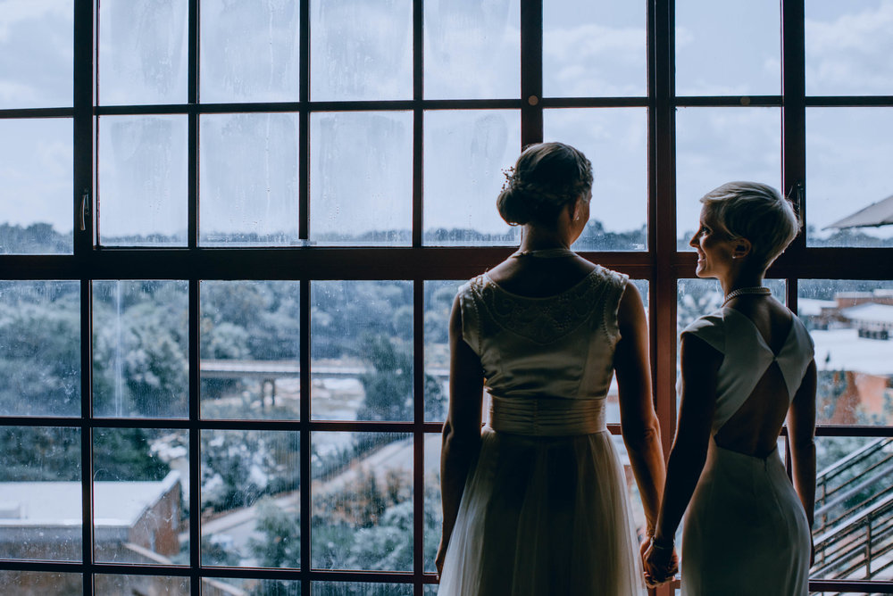 brides looking out the window from the haw river ballroom in saxapahaw north carolina