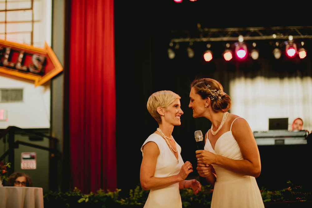brides sharing a welcome toast to their guests at the start of their haw river ballroom wedding reception