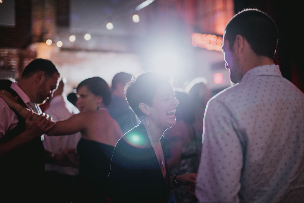 guests having a laugh while dancing during the wedding reception at the haw river ballroom
