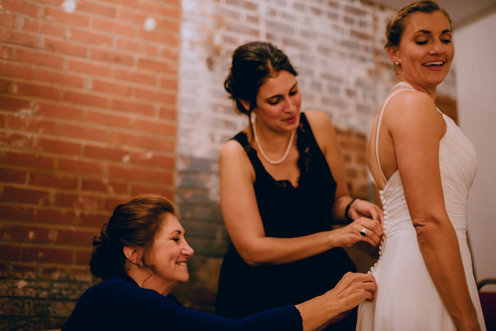 bride changing into her second dress with help of her sister and mother during haw river ballroom