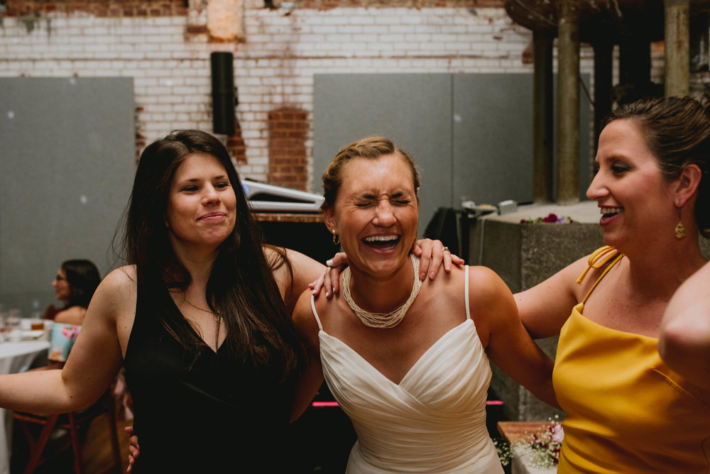 bride sharing a laugh with friends during haw river ballroom wedding