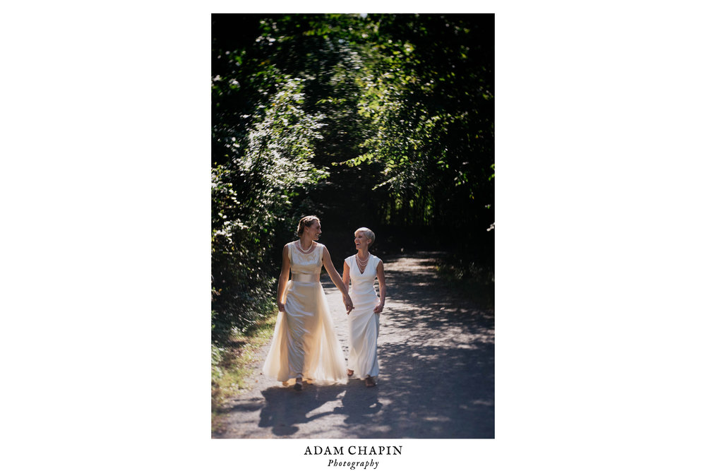 brides walking the trails around saxapahaw together before their wedding ceremony
