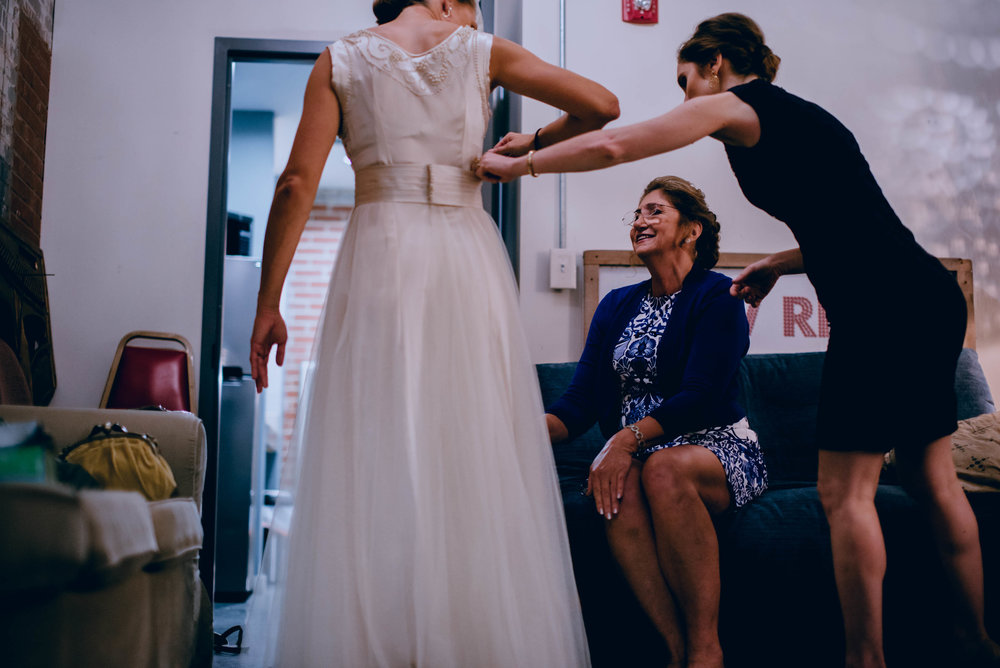 finishing touches of getting bride ready in her wedding dress