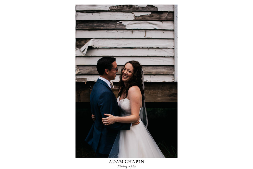 bride and groom laughing with one another in front of a dilapidated house before their wedding ceremony