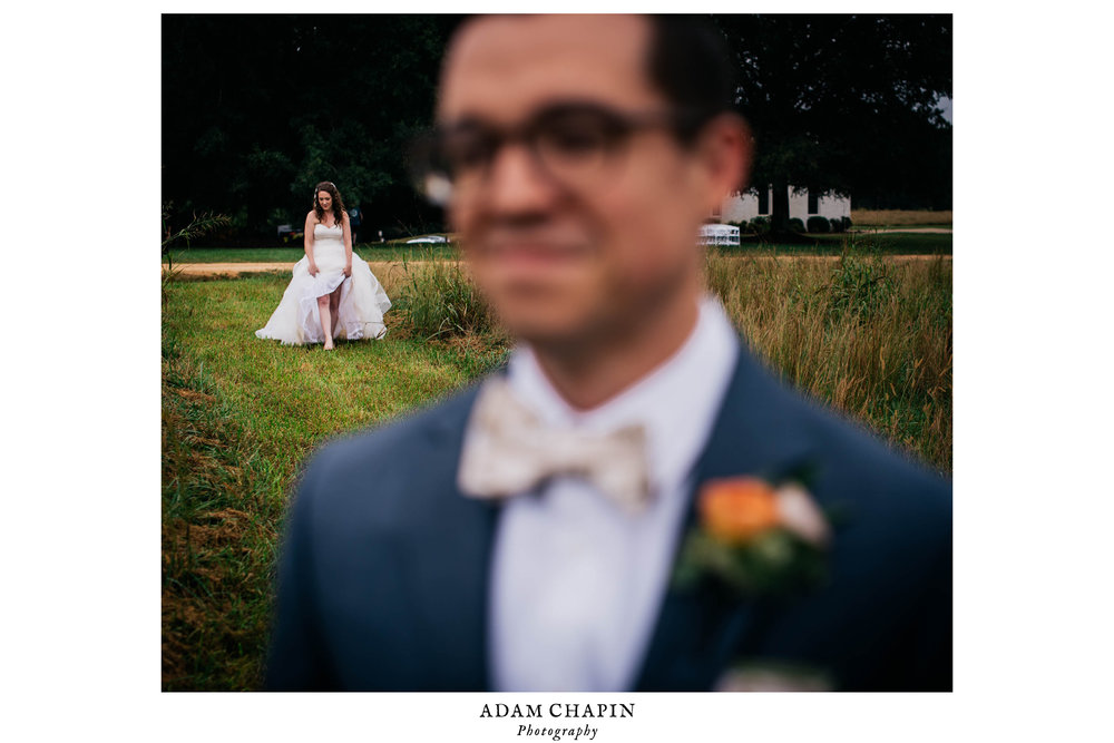 groom blurred out in the foreground as his bride is walking up from behind though the field for their first look