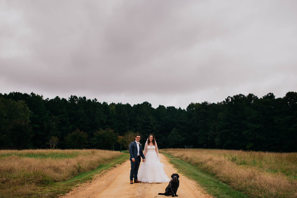 bride and groom standing in the drive of the Meadows Raleigh with their black labrador retriever sitting in front of them