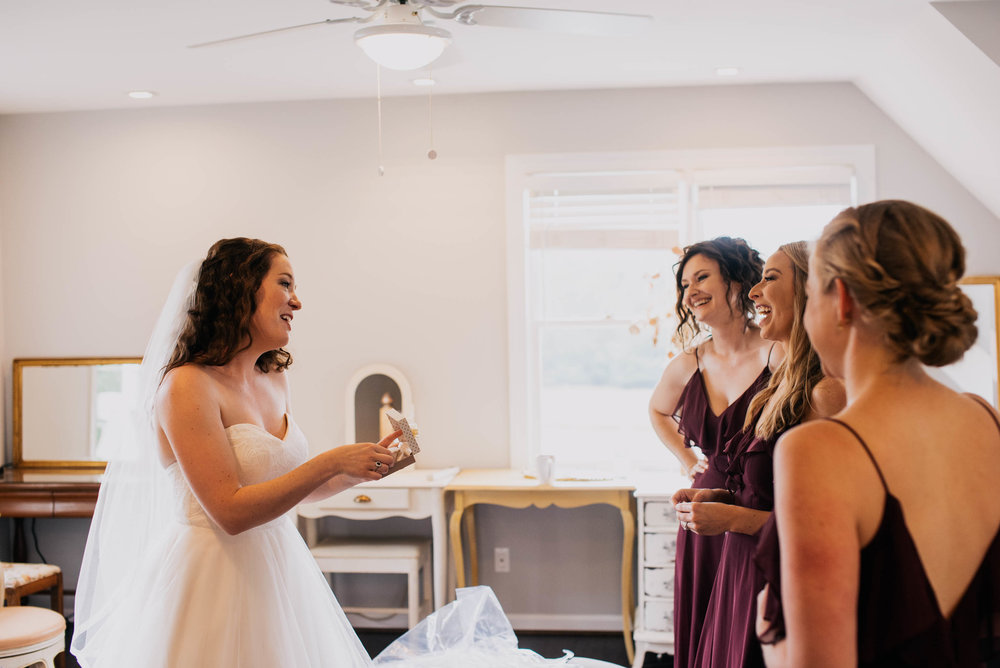 bride opening a wedding gift to her from her bridesmaids