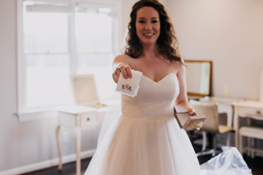 bride showing off her wedding gift from her bridesmaids