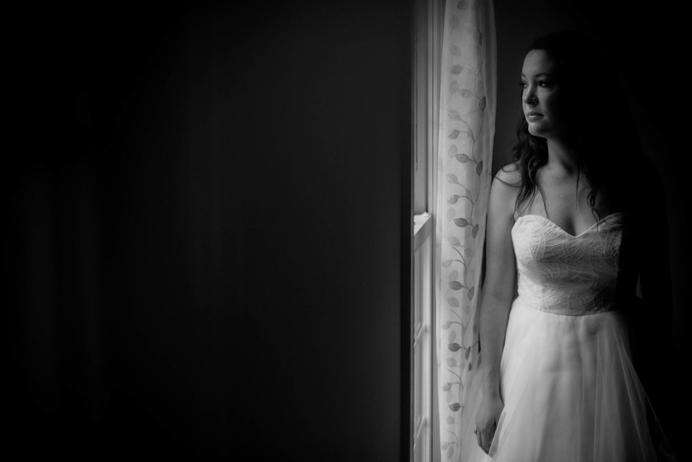 black and white photo of the bride looking out the window before the ceremony