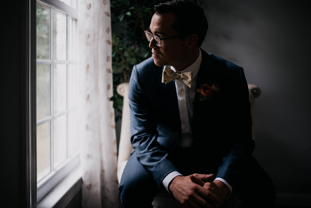 groom sitting in a chair and looking out the window right before the wedding ceremony