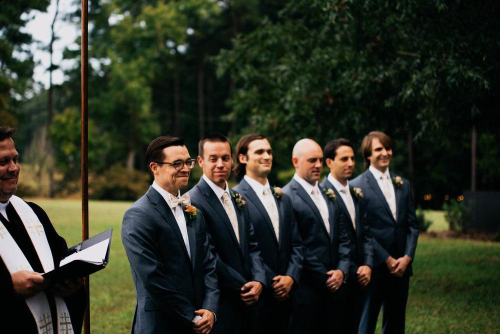 groom and his groomsmen watching the bride walk down the aisle