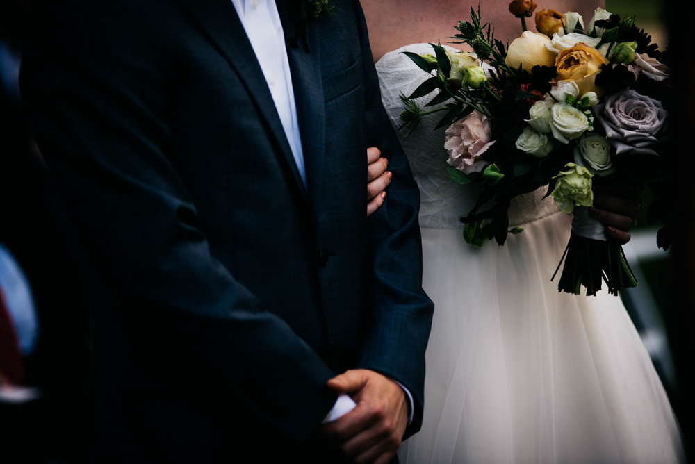 a cropped photo of the bride holding on to the groom during their wedding ceremony