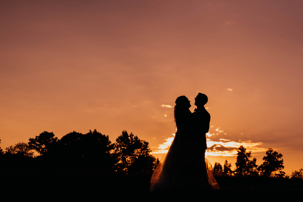 bride and groom standing in the pink and orange sunset as they are silhouetted by the sun