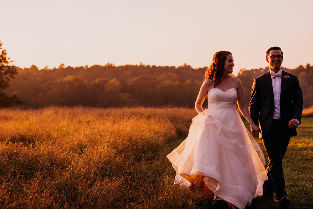 bride and groom walking in the sunset next to a field during their wedding day