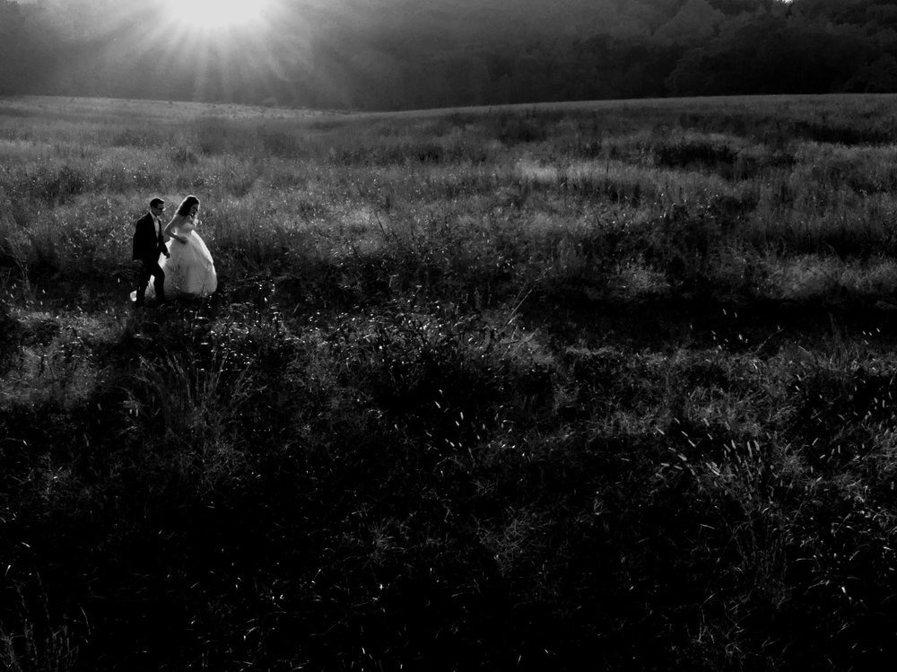 black and white drone photo of the bride and groom walking into a field as the sun sets off in the distance