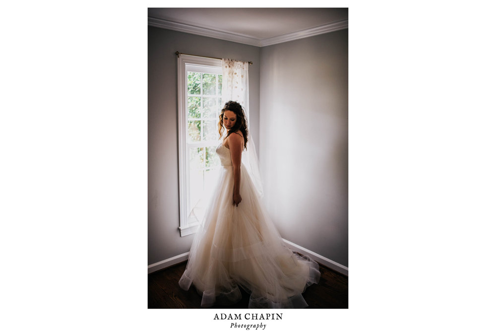 bride posing by a window in her wedding dress before her wedding ceremony