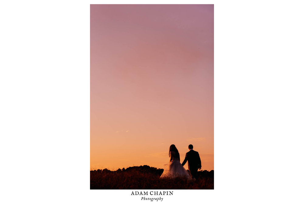 silhouette of bride and groom walking into the pink, peach and orange sunset