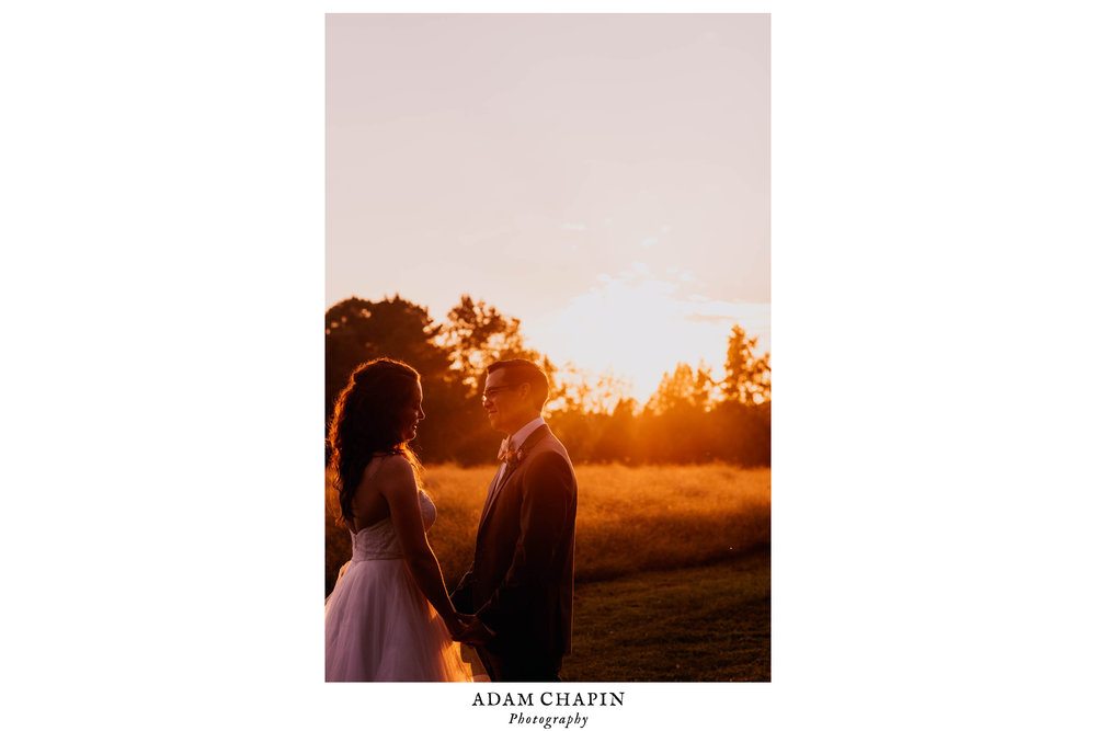 bride and groom standing by a meadow as the sun sets on their wedding day