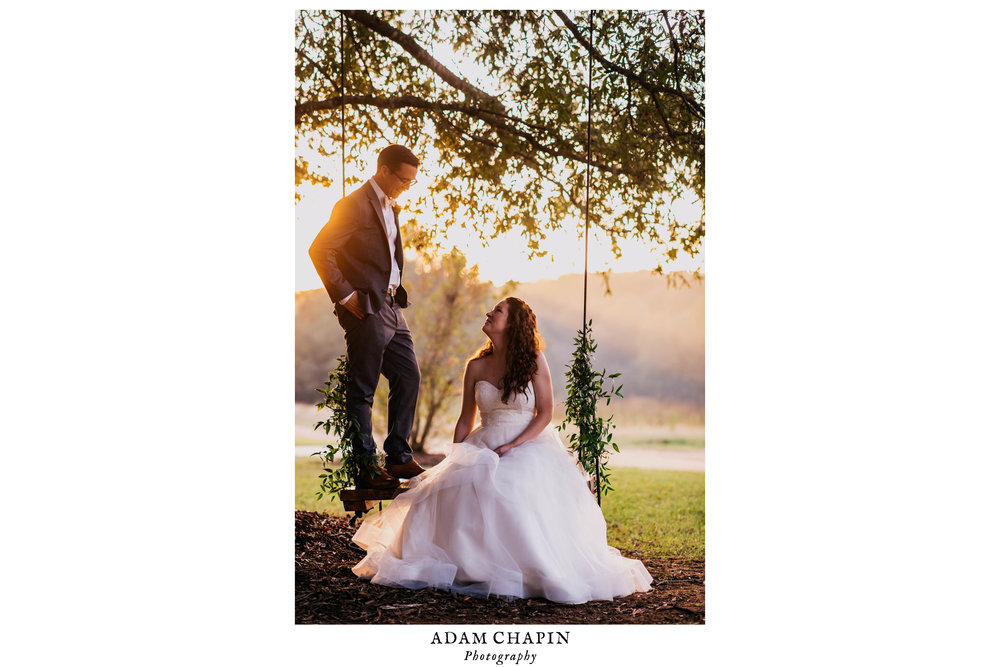 bride and groom atop the tree swing looking at each other during their wedding