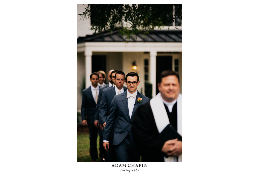 the groom, officiant and groomsmen walk down the aisle at the beginning of the ceremony