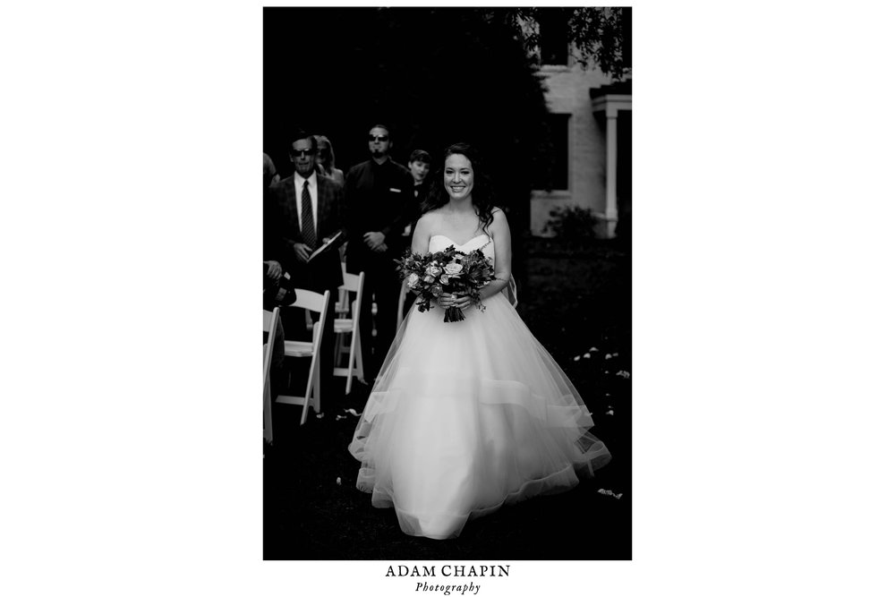 black and white photo of the bride walking down the aisle at the start of the wedding ceremony