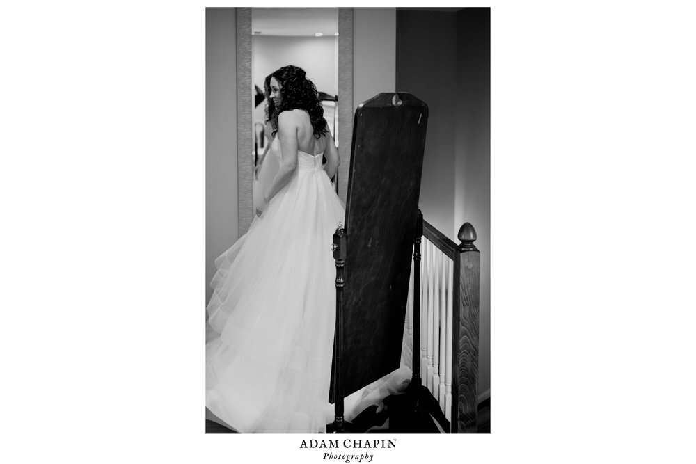 black and white photo of the bride doing on final look in the mirror before heading downstairs