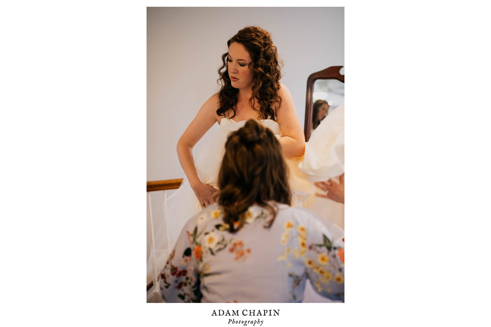 bride being helped with her wedding dress by one of her bridesmaids